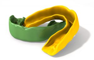 Two regular yellow and green moulded sports gum guards on an isolated background