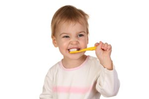 baby with tooth brush cleans the teeth isolated on white background